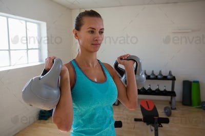 Confident female athlete lifting kettlebells in gym