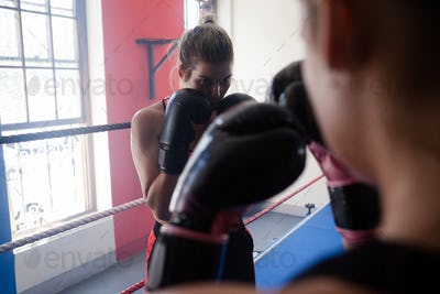 Trainer assisting woman in boxing