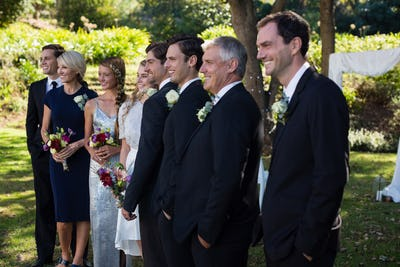 Happy bride and groom standing with guests