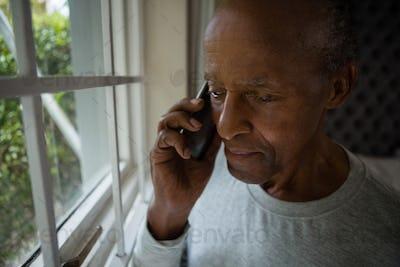 Serious senior man talking on mobile phone by window
