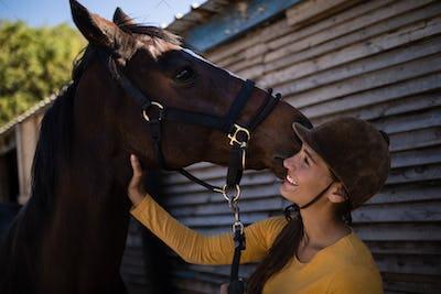 Happy female jockey stroking horse