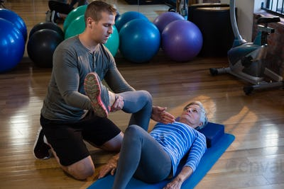 Male physiotherapist helping patient in performing exercise with resistance band