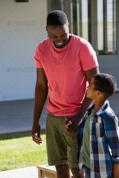 Father and son holding hands in the backyard