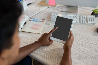 Cropped image of man using digital tablet in office