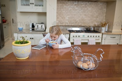 Young girl having breakfast in the kitchen