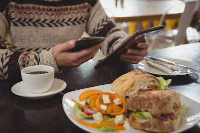 Mid section of man with breakfast using phone and tablet in cafe
