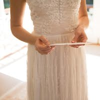 Midsection of bride holding wedding card at home