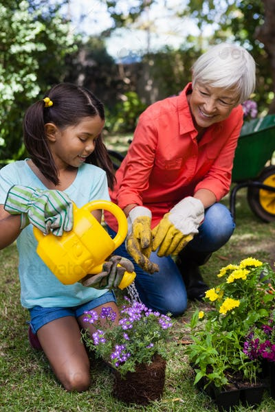 Smiling senior woman looking at girl watering flowers