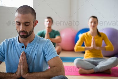 Yoga instructor with students meditating in prayer position at club