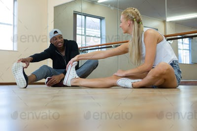 Full length of dancers stretching on wooden floor