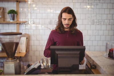 Young waiter with long hair using cash register at coffee shop