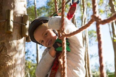 Little girl wearing helmet standing on rope fence