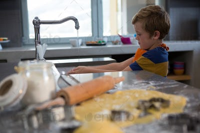 Boy washing hands in kitchen