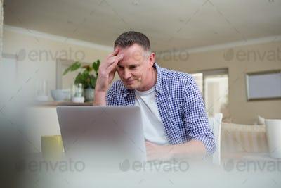 Worried man using laptop in living room