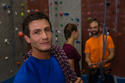 Portrait of confident man with climbing rope in gym