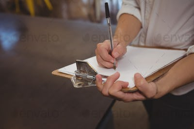 Mid section of waitress writing on paper