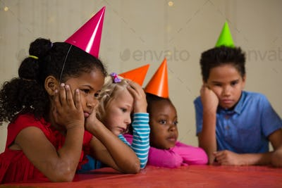 Tired children wearing party hat at table