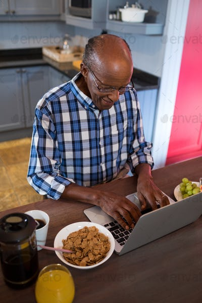 High angle view of senior man using laptop in kitchen