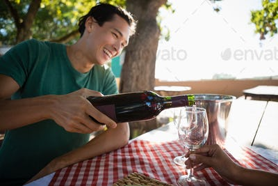 Smiling man pouring wine in glass held by friend