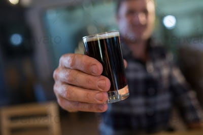 Close up of man holding beer glass at bar