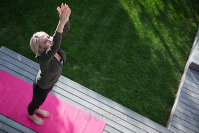 Overhead of woman practicing yoga in porch