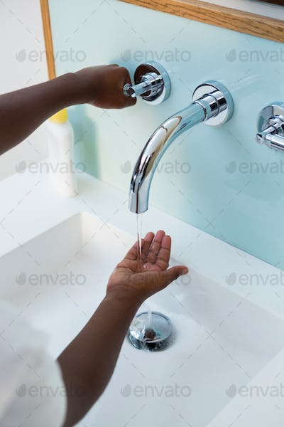 High angle view of boy washing hands in wash bowl