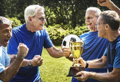 Team of mature football players winning the cup