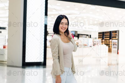 Beautiful woman in mall smiling after shopping