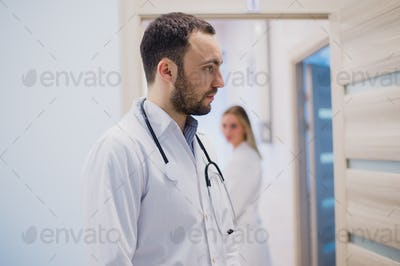 Sad pensive doctor staying in hospital corridor