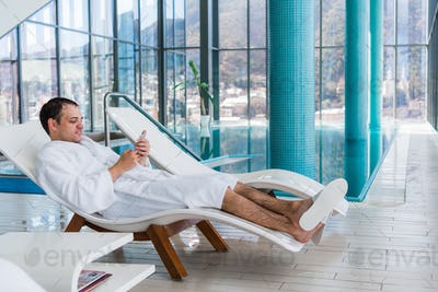 Young Man Resting On Sun Loungers By Swimming Pool And using Mobile Phone