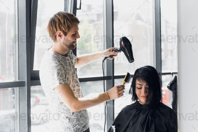 Young woman getting her hair dressed in hair salon by a handsome hairdresser hairstylist