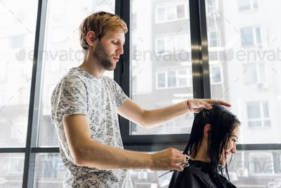 The hairdresser does a haircut with scissors of hair to a young girl in a beauty salon.