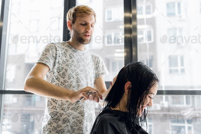 Male hairdresser makes hairstyle for a girl at hair salon.