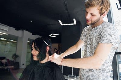 Hairstylist with comb and scissors cutting hair of female client. Woman in hairdressing beauty salon