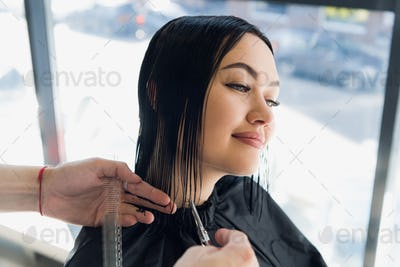 Young beautiful woman having her hair cut at the hairdresser's. Enjoying the process of making a