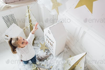 Little girl with house models and stars decoration