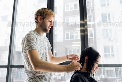 Hairdresser cutting hair of a beautiful serious brunette woman