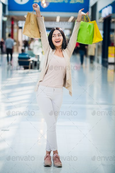 A dark-haired woman wearing muted, gentle colours holds colourful, patterned shopping bags walks at