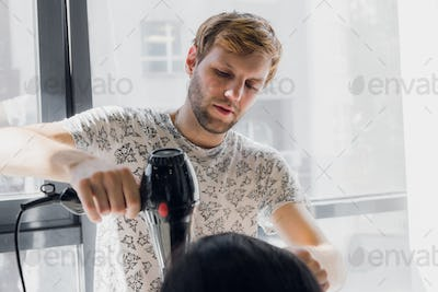 Professional smiling male stylist blow drying woman's hair with a dryer in salon