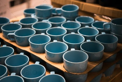 Colorful cup store. Aqua blue color cups standing In shop.
