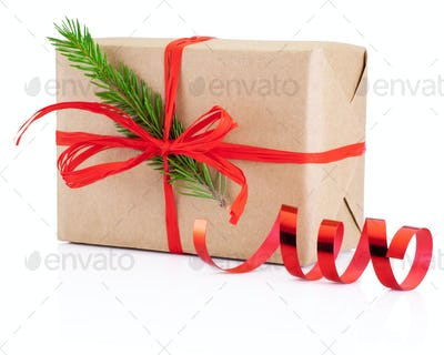 Christmas gift in kraft paper tied red braid and pine tree branc