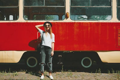Carefree hipster girl posing with tram in background