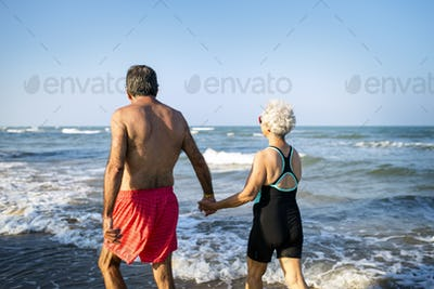 Mature couple walking into the water