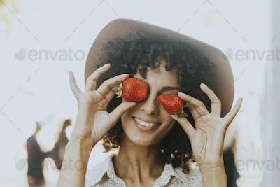 Woman having fun with strawberries