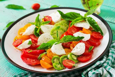 Mozzarella cheese, tomatoes and basil herb leaves in plate on the white wooden table.