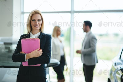 Professional saleswoman working in car dealership