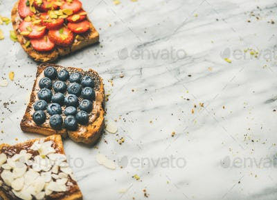 Vegan whole grain toasts with fruit, seeds, nuts, marble background