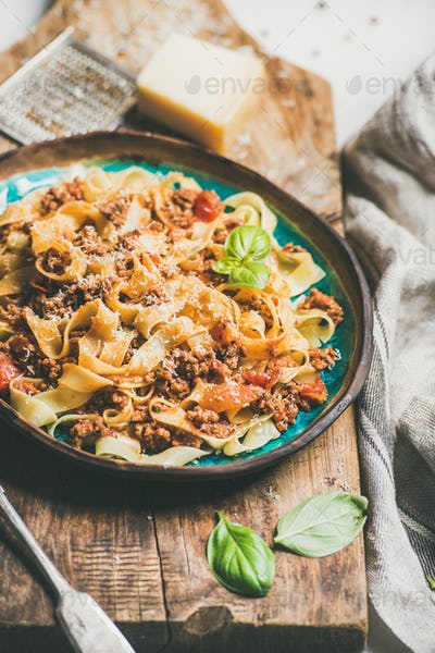 Italian traditional pasta dinner with tagliatelle bolognese and tomato sauce