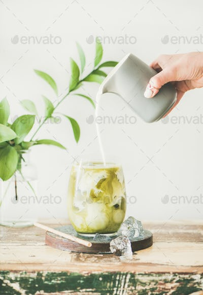 Iced matcha latte with milk pouring fron pitcher in glass