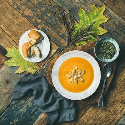 Warming pumpkin cream soup with croutons and seeds, square crop